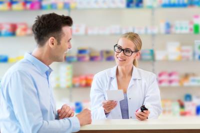 pharmacist wearing eyeglasses talking with the customer