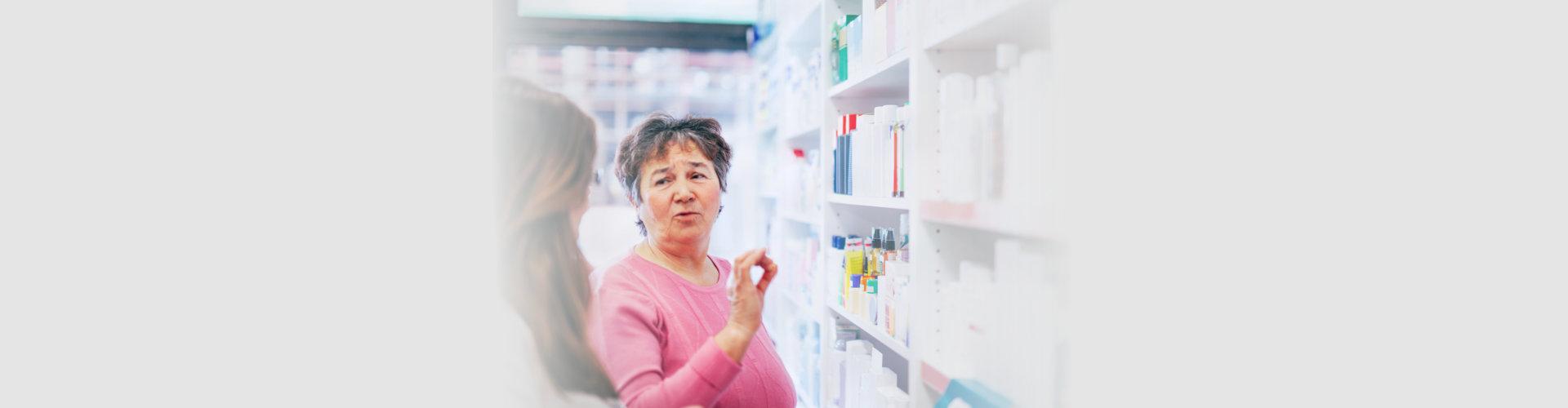 pharmacist discusses medication assortment with senior customer beside pharmacy shelf